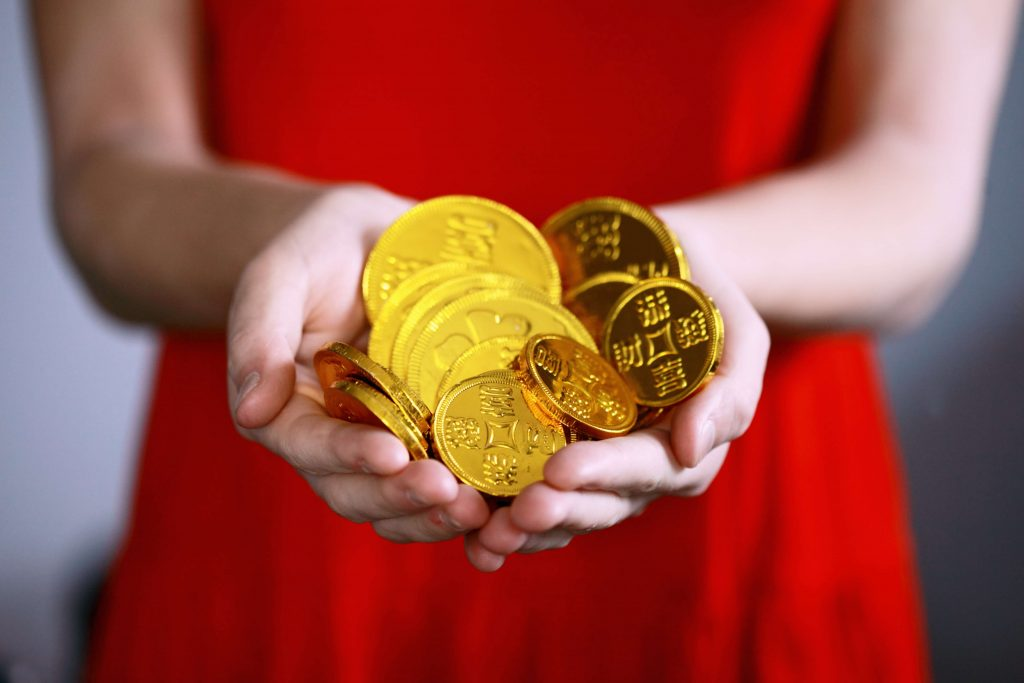 Woman holding gold coins in her hands. How we make $20K per month with our blogging business
